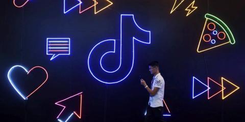 Un hombre pasa junto a un letrero de TikTok en la Exposición Internacional de Productos Artificiales en Hangzhou, China, en octubre de 2019.