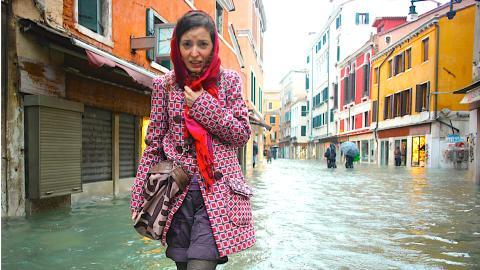 Una mujer camina por una calle inundada durante el periodo de marea alta en Venecia, Italia
