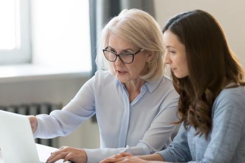 Una mujer enseña junto a una chica joven frente a un ordenador