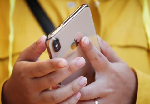Mujer con un iPhone en la mano.