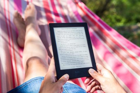 Mujer leyendo un libro en un lector de libros electrónico