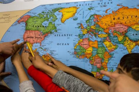 Niños señalando un mapa del mundo.
