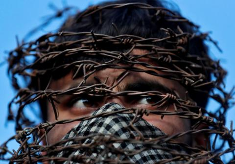 On October 11, a masked Kashmiri man with his head covered with barbed wire attends a protest after Friday prayers during restrictions following the Indian government's scrapping of the special constitutional status for Kashmir in