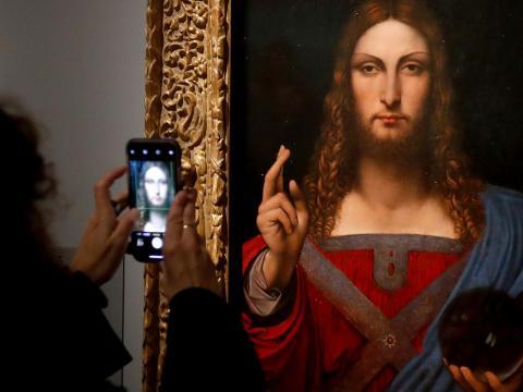 """Una persona fotografía """"Salvator Mundi""""."""