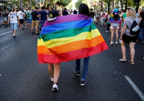Una pareja pasea por el Paseo del Prado de Madrid con la bandera Gay.