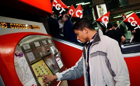 Un pasajero compra un billete de Cercanías ante unos piquetes de CGT