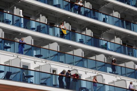 Pasajeros en los balcones de los camarotes de un crucero.