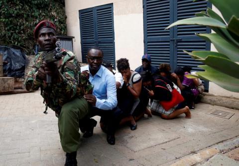 Varias personas son evacuadas por un miembro de las fuerzas de seguridad en el lugar donde se escucharon explosiones y disparos en el complejo del hotel Dusit en Nairobi, Kenya, el 15 de enero.