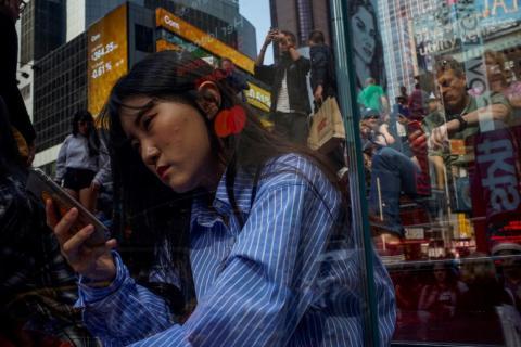 La gente mira sus móviles en Times Square en la ciudad de Nueva York el 8 de mayo.
