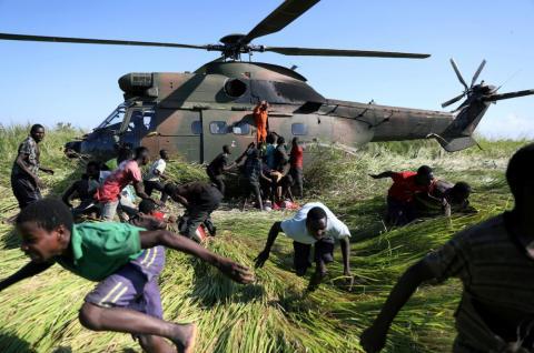 Varias personas huyen tras recoger ayuda alimentaria de un helicóptero de la Fuerza de Defensa Nacional de Sudáfrica (SANDF) tras el ciclón Idai en la aldea de Nhamatanda, cerca de Beira, Mozambique, en marzo.
