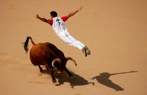 Un recortador salta sobre un toro durante un concurso en la plaza de toros Monumetal de Pamplona durante las fiestas de San Fermín, el 13 de julio.