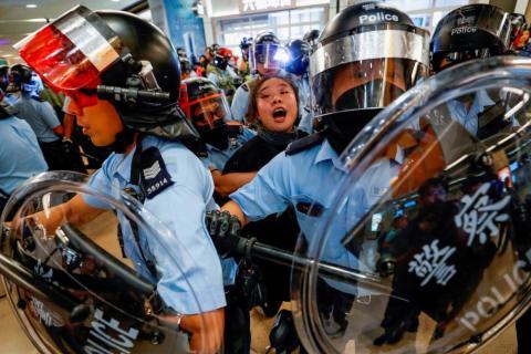 La policía antidisturbios de Hong Kong detiene a una mujer mientras los manifestantes se reúnen en la estación del ferrocarril, Sha Tin (MTR), el 25 de septiembre.