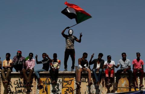 Un manifestante sudanés con una máscara de Guy Fawkes ondea una bandera nacional frente al recinto del Ministerio de Defensa en Jartum, Sudán, el 24 de abril. Las semanas de protestas finalmente provocaron la dimisión de Omar al-Bashir.