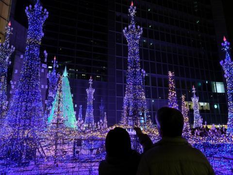 Los turistas admiran las iluminaciones basadas en populares películas animadas de Disney para la temporada de invierno en el centro de iluminación de invierno Caretta Shiodome en Tokio el 16 de diciembre de 2018.