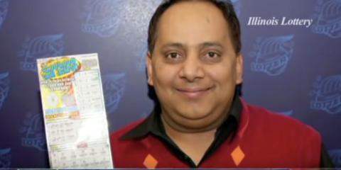 Urooj Khan posando con su billete de la lotería premiado.