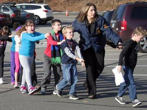 Una oficial de policía conduce a niños de la escuela primaria Sandy Hook.