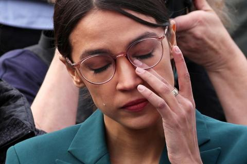 U.S. Representative Alexandria Ocasio-Cortez wipes away tears as Representative Ilhan Omar talks about her own experience as a refugee during a news conference calling on Congress to cut funding for ICE (Immigration and Customs