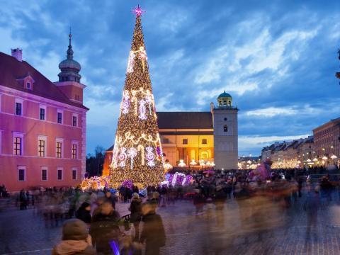 Árbol de Navidad y la gente en la Plaza del Castillo en el casco antiguo de Varsovia, Polonia, iluminada al atardecer.
