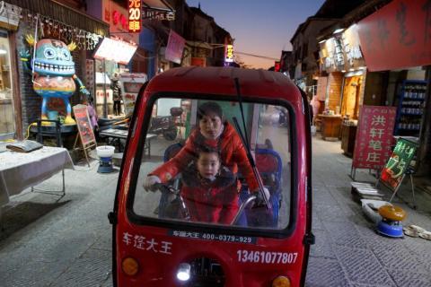 Una mujer y un niño montan un triciclo eléctrico en el casco antiguo de Luoyang, provincia de Henan, China, en enero.
