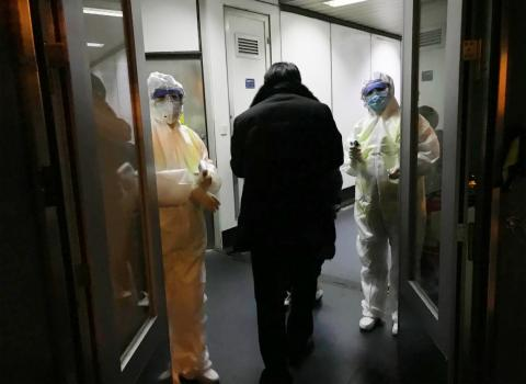Health officials in hazmat suits checking body temperatures of passengers arriving from Wuhan on January 22 at the airport in Beijing.