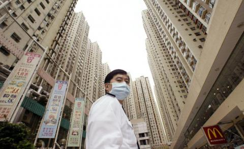 A security guard wears a mask at Amoy Gardens housing estate in Kowloon bay, Hong Kong, where a block was quarantined to protect against a SARS outbreak, April 1, 2003.