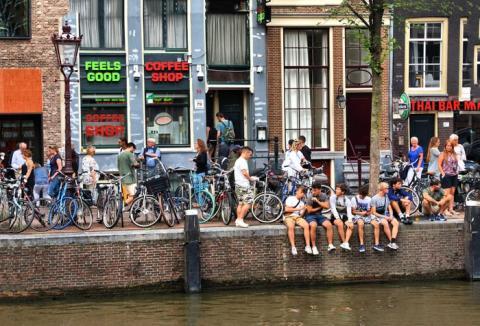 Los turistas se relajan a lo largo de un canal en Amsterdam.