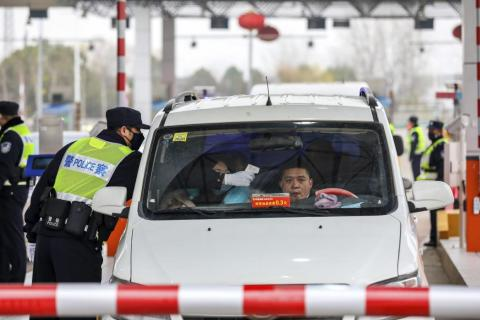 A policeman uses a digital thermometer to take a driver's temperature at a checkpoint at a highway toll gate in Wuhan, China on January 23, 2020.