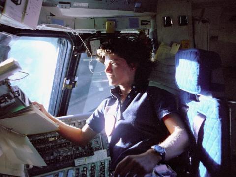 Sally Ride, la primera astronauta estadounidense en el espacio, monitoriza los paneles de control desde la cubierta de vuelo.