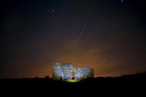 Las estrellas cruzan el cielo sobre un teatro romano en las ruinas de Acinipo, cerca de Ronda, España, durante la lluvia de estrellas Perseida del 13 de agosto de 2015.