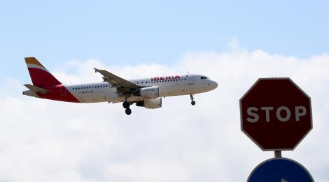 Un avión de Iberia vuela sobre el aeropuerto de El Prat de Barcelona.