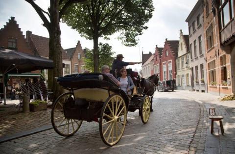 Los turistas viajan en un coche de caballos en Brujas, Bélgica, en 2016.