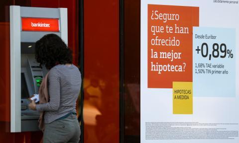 Una clienta usa un cajero automático en una sucursal bancaria ante un anuncio de hipotecas