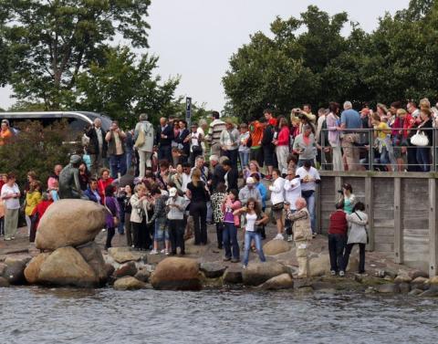 Turistas se agolpan alrededor de la estatua de la Sirenita en Copenhague.