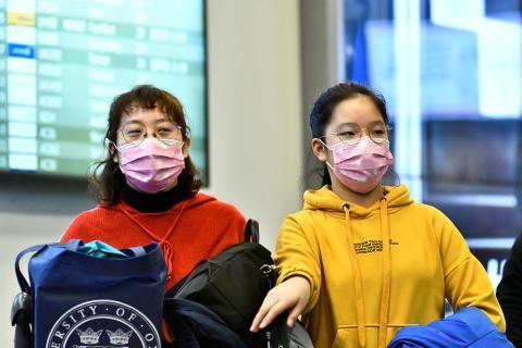 Los viajeras llevando máscaras llegan al aeropuerto de Vancouver, Canadá, desde China.