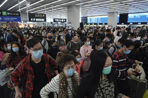 Passengers wear protective face masks at the departure hall of the high-speed train station in Hong Kong, January 23, 2020.