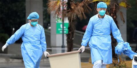 Dos médicos chinos transportan material sanitario en la ciudad de Wuhan