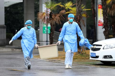 Dos médicos transportan una caja con material sanitario en un hospital de Wuhan, donde permanecen ingresados varios pacientes con el coronavirus de Wuhan.