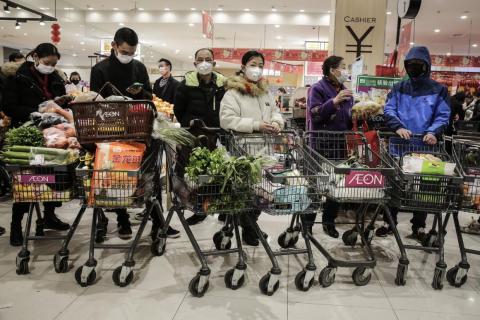 Los residentes de Wuhan usan máscaras cuando compran alimentos el 23 de enero de 2020.