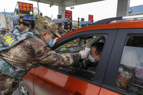 A militia member uses a digital thermometer to take a driver's temperature at a checkpoint at a highway toll gate in Wuhan, China, January 23, 2020.