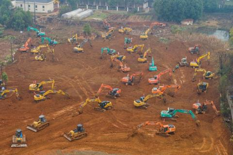 Excavators at the construction site of a new hospital being built to treat patients from a deadly virus outbreak in Wuhan.