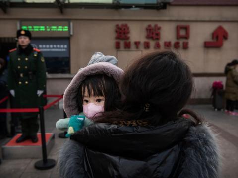 Una niña con una mascarilla en una estación de tren de Pekín.