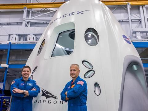 Behnken (izquierda) y Hurley (derecha) posando frente a la maqueta de la nave Dragon de SpaceX en el Centro Espacial Johnson de la NASA.