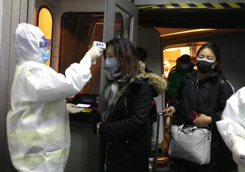 Health officials in hazmat suits check body temperatures of passengers arriving from Wuhan, China, on January 22, 2020, at the airport in Beijing.
