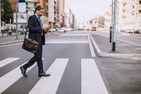 Hombre con el móvil cruzando la calle