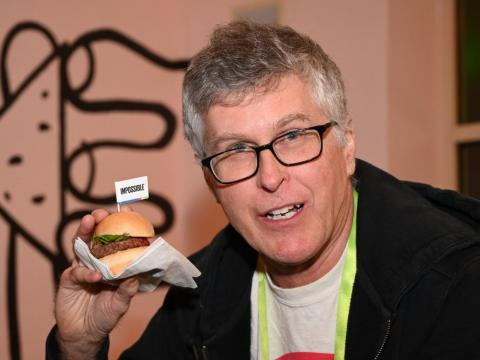 Impossible Foods CEO Pat Brown holds up an Impossible Burger 2.0, the new and improved version of the company's plant-based vegan burger that tastes like real beef.