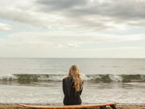 Una mujer surfista mirando al mar