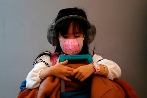 Una niña con mascarilla espera en una estación de Hong Kong