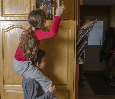Niños tratando de coger algo en la despensa
