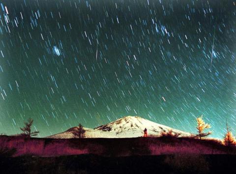 En esta foto de 7 minutos de exposición, sobre el nevado monte Fuji en Japón, el 19 de noviembre de 2001, se ven estrellas Leonidas por el cielo.