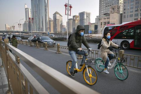 A couple wear face masks as they ride along a street in Beijing, Wednesday, Jan. 22, 2020.